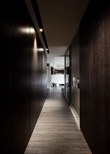 在公共空間過渡至私領域的廊道以深色刀痕鋼刷木皮的深色基調圍塑成熟穩重的氛圍,點綴以大地色系,做為公私領域的歇心轉折。