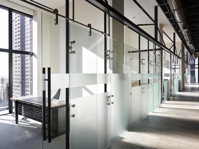 長廊的一側是各主管室的所在地,運用不同但有規律的噴砂處理,使玻璃的清透,帶上一層機能各異,卻又整齊畫一的面紗。