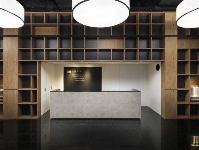 接待櫃台同樣施以清水模造型的設計,崁入在大量木質開放櫃內,用白色系的空間明確的讓兩者間產生界線增加立體感,在意象上也為了清水模至木質間的材質轉換埋下伏筆。