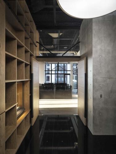 與入口接待櫃台相對的是清水模造型牆面,順應梯間的清水模設計,在大廳處進行一個材質的轉換,上方的圓型訂製吊燈,用意則為軟化空間硬度。
